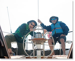 photo of Sheehan and Dingee on the helm of their  sailboat